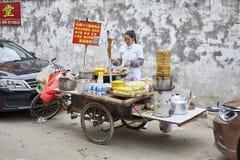 La femme prépare et vend la nourriture de petit déjeuner de la stalle de rue Photographie stock