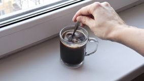 La femme prépare le café soluble dans une tasse en verre transparente sur un filon-couche de fenêtre pendant le matin et le remue clips vidéos