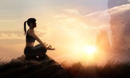 La femme pratique le yoga méditant à est un asana sur une pierre, coucher du soleil image stock