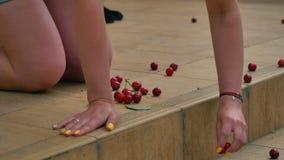 La femme prenant des cerises a dispersé sur le porche clips vidéos