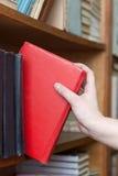 La femme prend le livre rouge de l'étagère Image stock