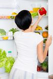 La femme prend le poivron rouge du réfrigérateur ouvert Photos stock