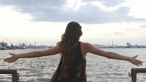 La femme prend lentement les mains et saute dans la mer La vue arrière banque de vidéos