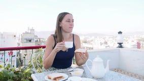 La femme prend un petit déjeuner en café sur la terrasse sur le fond de ville et de montagne clips vidéos