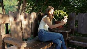 La femme prend un selfie dans la perspective des fleurs la femme s'assied sur une boutique en bois près des fleurs banque de vidéos