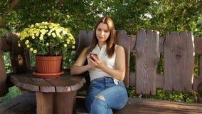 La femme prend un selfie dans la perspective des fleurs la femme s'assied sur une boutique en bois près des fleurs envoie des pho banque de vidéos