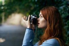 La femme prend une photo sur un appareil-photo de film sur une avenue dans la ville images stock