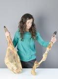 La femme prennent le jambon un fini et un entier différent du serrano deux photos libres de droits