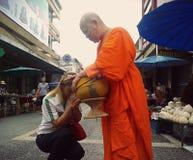 La femme prie après avoir donné l'aumône à la nonne bouddhiste Phayao, Thaïlande : image libre de droits