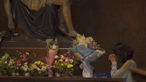 La femme prie avec la statue Vierge Marie et de Jésus banque de vidéos