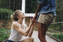 La femme proposant à son amie heureuse dehors aiment et à concept de mariage Photographie stock libre de droits