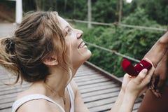 La femme proposant à son amie heureuse dehors aiment et à concept de mariage Photographie stock