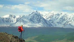 La femme que le voyageur coûte sur la roche et regarde des montagnes de neige Veste orange Sac à dos rouge clips vidéos