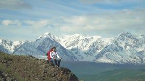 La femme que le voyageur se repose au dessus de montagne, prend le thé chaud d'un thermos Sac à dos rouge, veste orange Chapeau d banque de vidéos