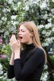La femme réagit avec l'asthme sur le rhume des foins tout en étant en parc Photographie stock libre de droits