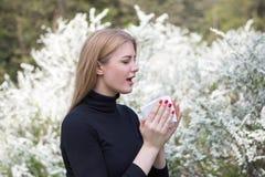 La femme réagit avec le pollen sur le rhume des foins tout en étant en parc Photographie stock libre de droits