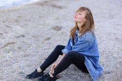 La femme réfléchie regarde le paysage marin et écoute le ressac, se reposant Photo stock