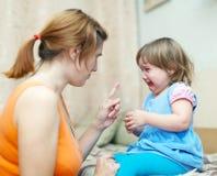 La femme réprimande le bébé pleurant Image stock