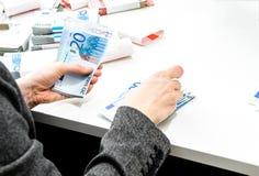 La femme réussie d'affaires compte l'ARO de factures d'argent un bureau Photos libres de droits