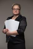 La femme réussie d'affaires n'est pas jeune dans un costume avec des papiers et Image stock