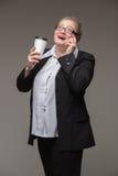 La femme réussie d'affaires n'est pas jeune dans un costume avec du café tal Photographie stock