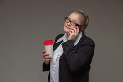 La femme réussie d'affaires n'est pas jeune dans un costume avec du café tal Image libre de droits