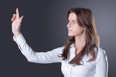 La femme réussie moderne d'affaires presse sur un bouton virtuel d'isolement dans l'obscurité images libres de droits