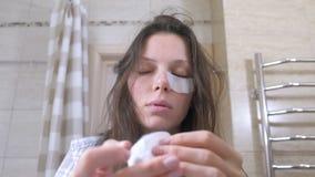 La femme réveillée fatiguée avec une gueule de bois met des corrections sur les yeux dans la salle de bains banque de vidéos