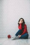 La femme rêveuse dans un chandail rouge et un coeur forment le cadeau Photographie stock libre de droits