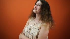 La femme rêveuse pensait à quelque chose, sur un fond orange banque de vidéos