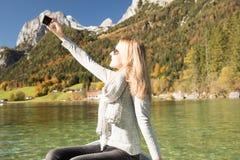 La femme rame avec un bateau à rames avec un lac dans les montagnes Image stock