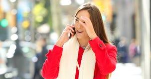 La femme recevant l'appel téléphonique le prend du sac banque de vidéos