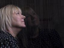 La femme regardant à l'intérieur hors d'une fenêtre a éclaboussé de la pluie Photos libres de droits