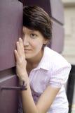 La femme regarde à l'extérieur par derrière le mur Image stock