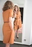 La femme regarde elle-même dans le miroir image stock