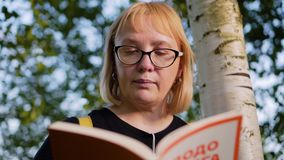 La femme regarde fixement la position de livre se penchant sur un tronc d'arbre Vue gentille de son visage La fille porte des lun banque de vidéos