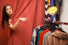 La femme regarde hors de la cabine d'essayage Photographie stock