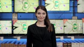 La femme regarde l'affichage à cristaux liquides TV dans le supermarché, boutique visuelle audio avec le beau conseiller Images libres de droits