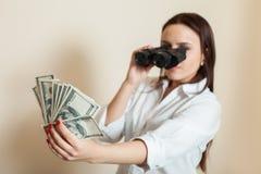 La femme regarde par des jumelles sur la fan d'argent Image stock