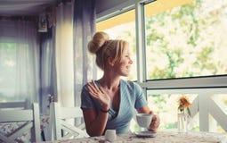 La femme regarde par la fenêtre, fond de nature Café et concept de date images stock