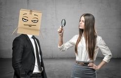 La femme regarde par une loupe un homme d'affaires avec une boîte sur sa tête avec un pokerface Photo libre de droits