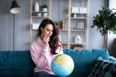 La femme regarde un modèle du globe se reposant sur un sofa image libre de droits