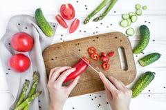 La femme remet couper en tranches le poivron doux sur la planche à découper en bois, entourée par des légumes Configuration plate photo stock