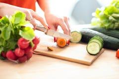 La femme remet couper le veg frais avec le couteau sur la planche à découper image libre de droits