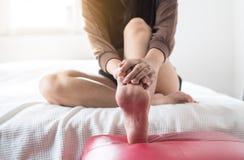 La femme remet donner le massage à son pied dans la chambre à coucher, massage de semelles de pied Photographie stock