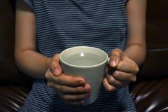La femme remet juger la tasse avec de l'eau l'eau douce intérieure et s'assied sur le brun image stock