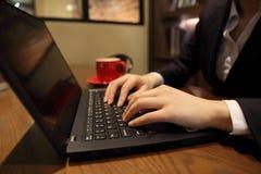La femme remet l'introduction au clavier un ordinateur portable dans un café Photographie stock