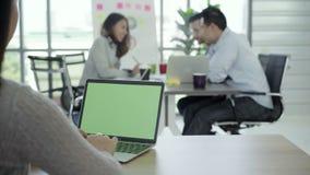 La femme remet l'ordinateur portable de dactylographie avec l'écran vert sur la table dans le bureau Plan rapproché clips vidéos