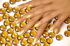 La femme remet la manucure avec le vernis à ongles d'or Photographie stock libre de droits