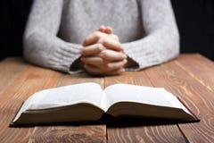 La femme remet la prière avec une bible dans l'obscurité au-dessus de la table en bois Images stock